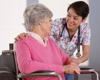 Domestic nurse talking with Older patient in wheelchair